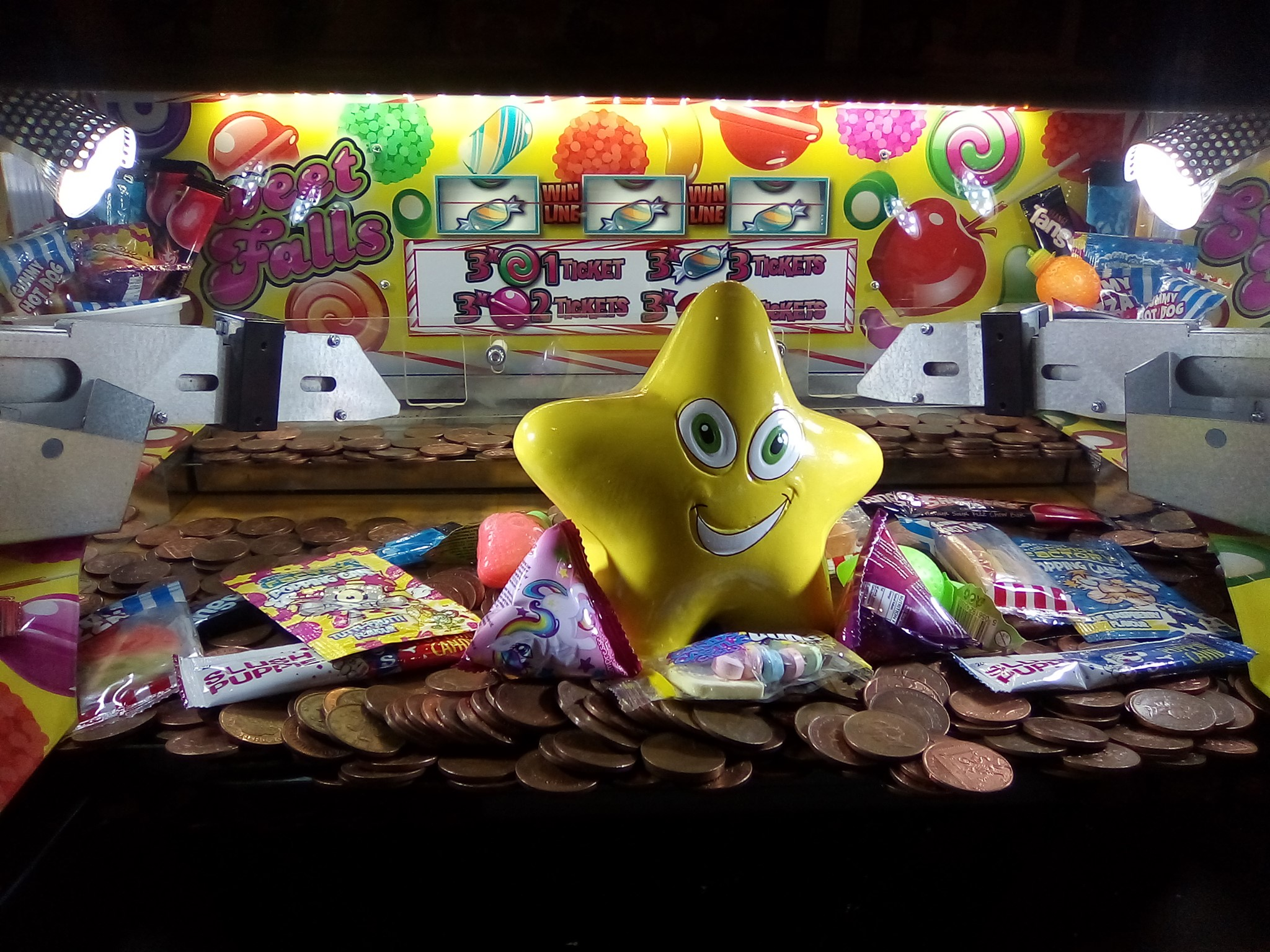 A shiny yellow star and some packets of sweeties sit on top of a pile of 2ps in a fairground machine.