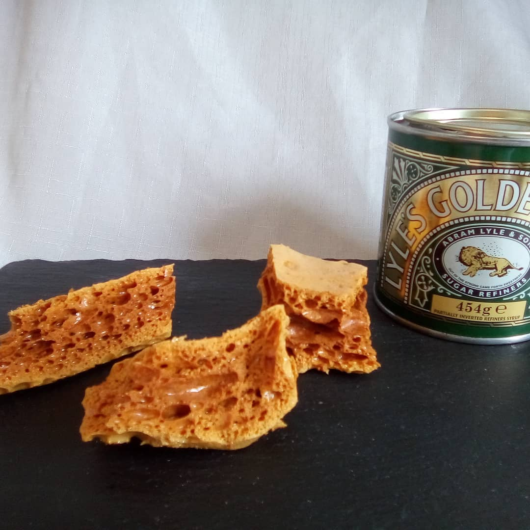 3 big pieces of cinder toffee sit next to a green tin of golden syrup.