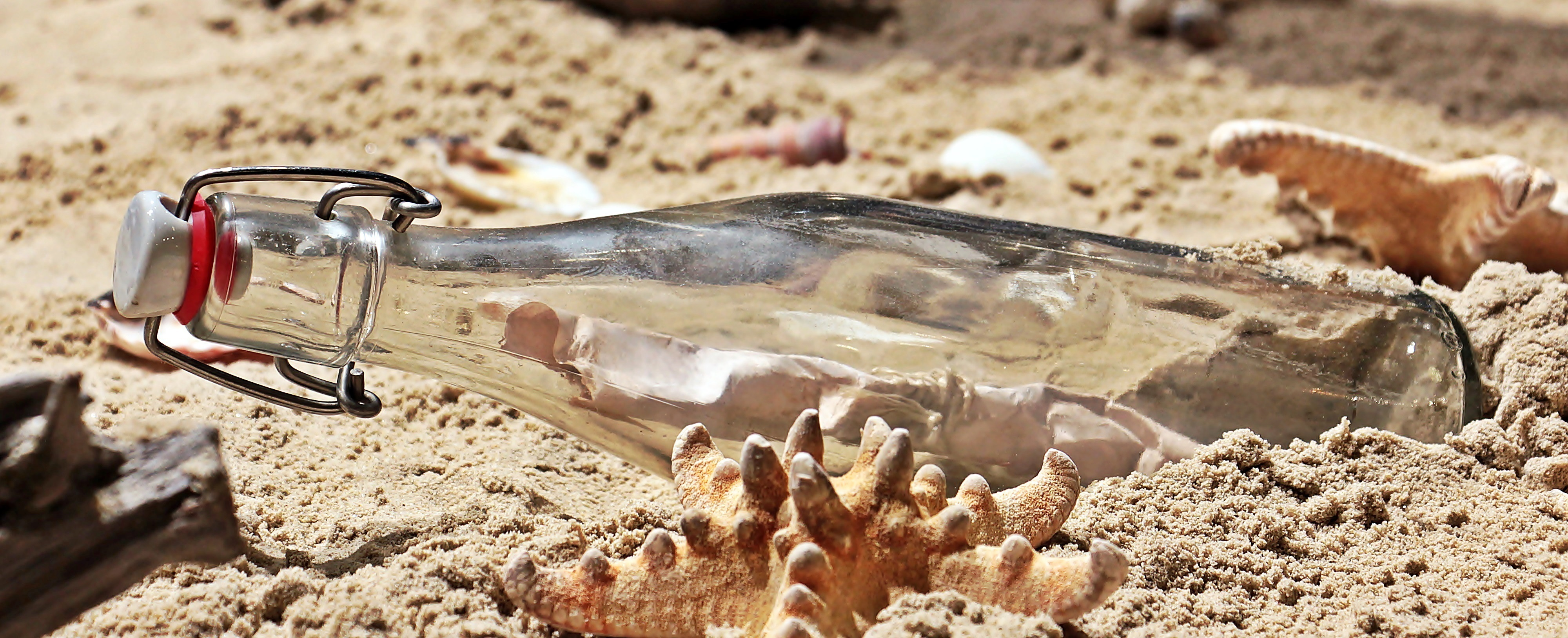A glass bottle lies on its side on the sand. There is a message inside.