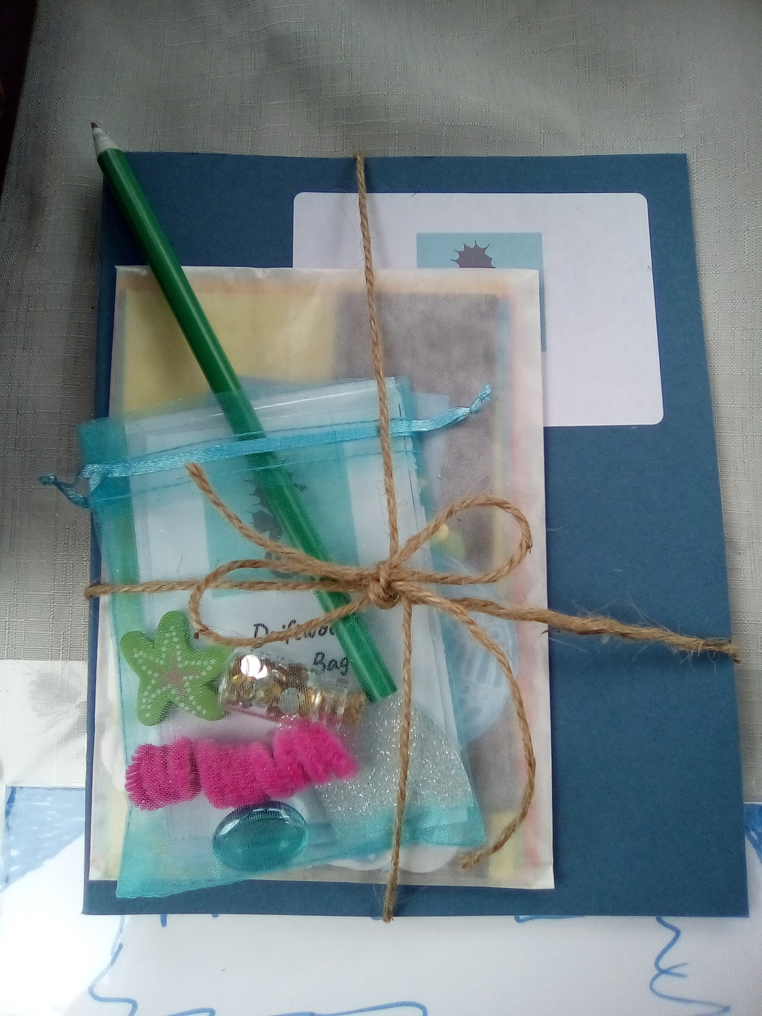 A package tied with string - a bag of interesting objects, a notebook and a pencil.